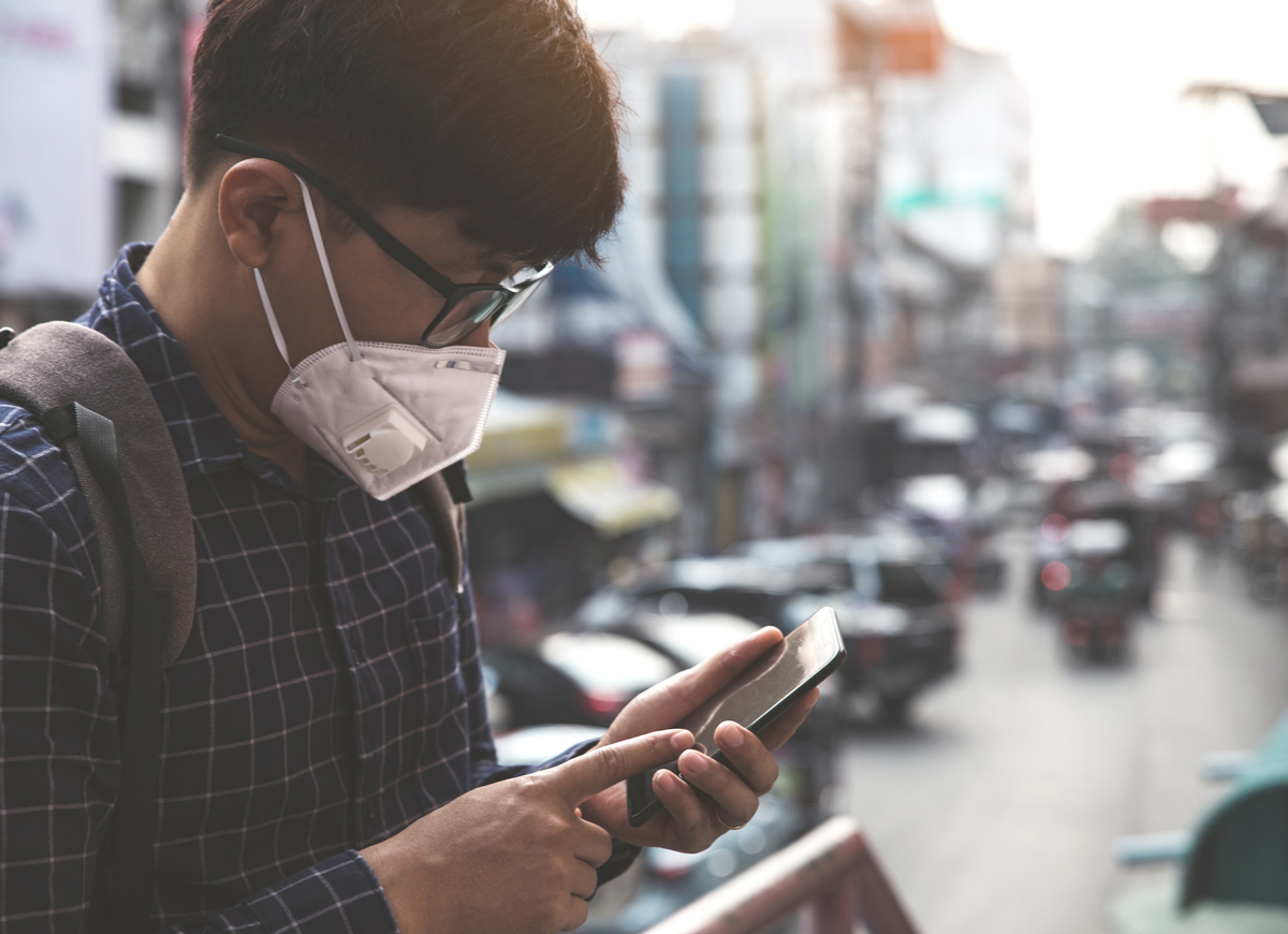 Man wearing n-95 mask while on his phone