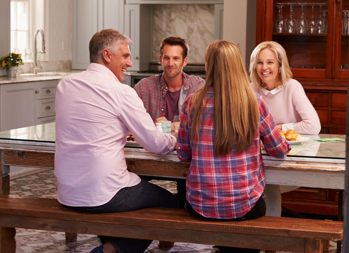 Multi-generational family having a conversation on the dinner table