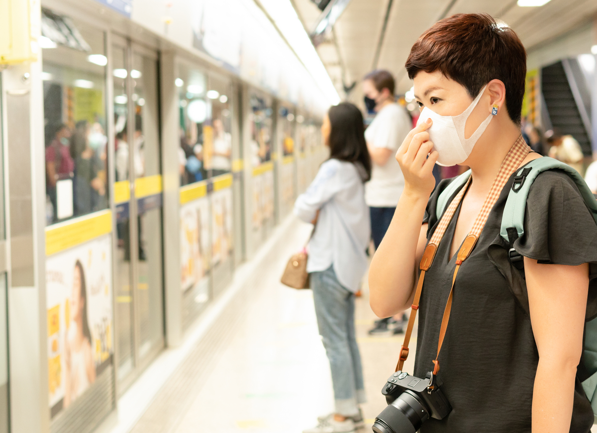 Woman waiting for subway wearing face mask.
