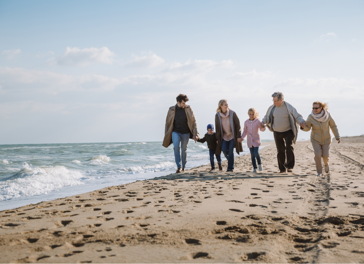 multi-generational family walking together on a beach