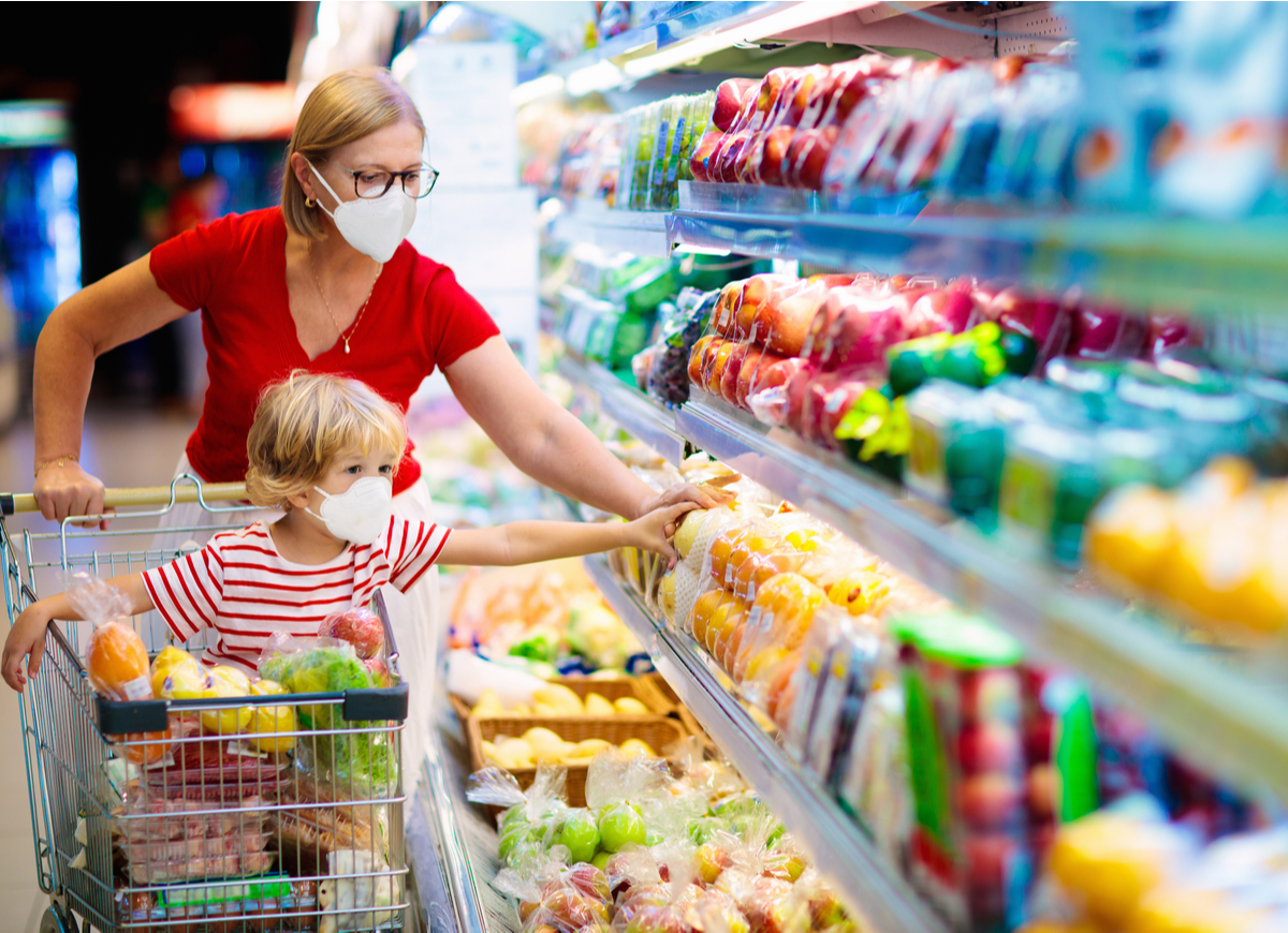 Woman with child wearing masks in grocery store